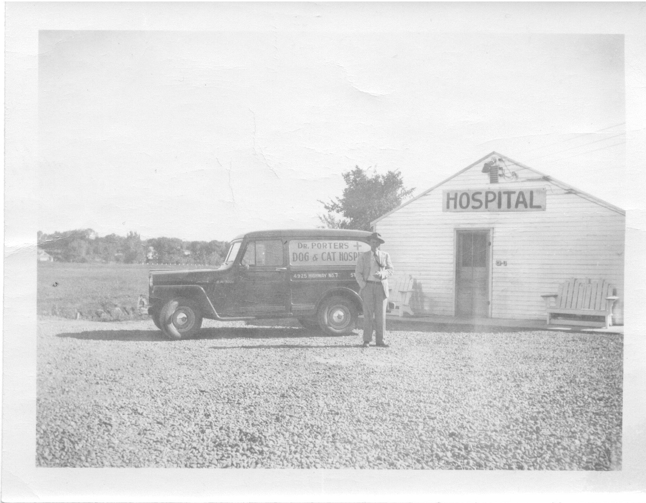 Dr. Porter Sr. standing next to the mobile veterinary truck in front of the temporary Park Pet Hospital Building